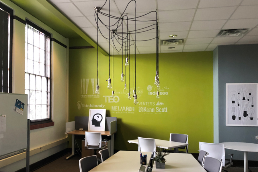 Inside a small biz office space with a whiteboard, and bright yellow-green walls with letters on it